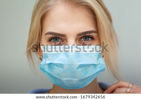 Beautiful Women In A Medical Mask. Close-up of a young woman with a surgical mask on her face against SARS-cov-2. #1679342656