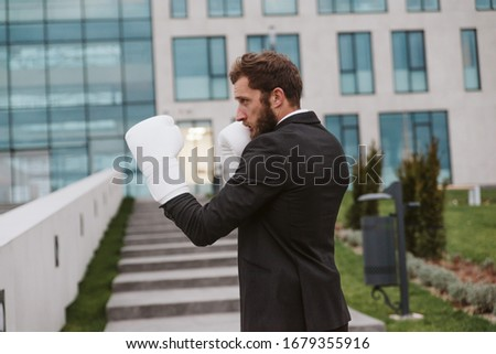 Businessman with boxing gloves is ready for corporate battle #1679355916
