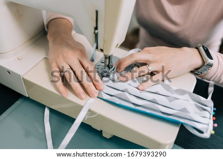 Woman hands using the sewing machine to sew the face medical mask during the coronavirus pandemia. Home made diy protective mask against virus. #1679393290