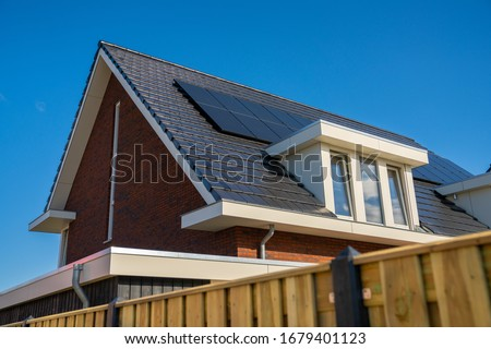 Horizontal close-up image of modern urban home dark roofing, white dormer and solar panels. Black tiled roof with dormer in the Netherlands. Photovoltaic installation rooftop, alternative electricity. #1679401123