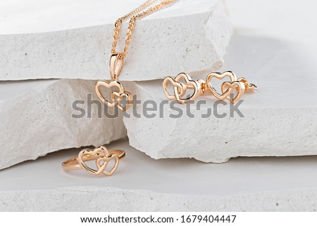 Jewellery set of hearts shape rose gold ring, pendant necklace and stud earrings on white background. Romantic  jewelry. Advertising still life product concept for Valentines Day #1679404447