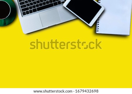 Office supplies are tablet, pen, computer, notebook, mobile phone and red coffee mug placed at an office desk. #1679432698
