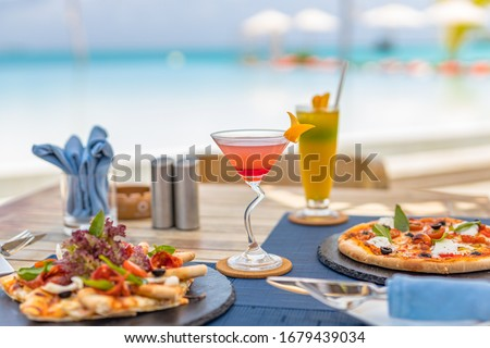 Pizza and tropical cocktail with beautiful sunny vacation infinity swimming pool ocean view. Beach restaurant, sea view, glasses, plates, food, tropical cocktail, blur loungers, chairs, sun umbrellas #1679439034