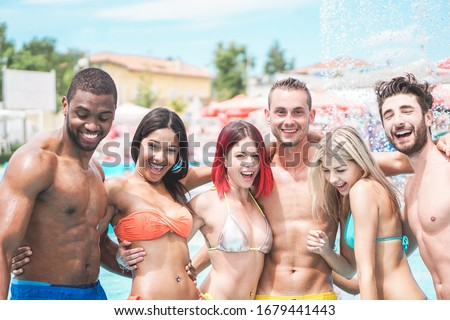 Happy friends playing in swimming pool party - Young diverse culture people having fun on summer vacation - Focus on center man face - Youth lifestyle, travel, holidays and friendship concept #1679441443