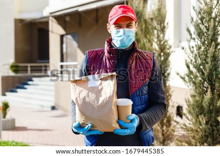 Delivery man holding paper bag with food on white entrance of house background , food delivery man in protective mask #1679445385
