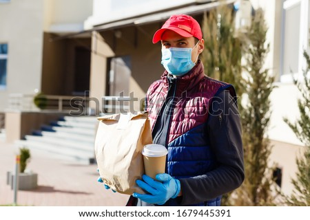 Courier in protective mask and medical gloves delivers takeaway food. Delivery service under quarantine, disease outbreak, coronavirus covid-19 pandemic conditions. #1679445391