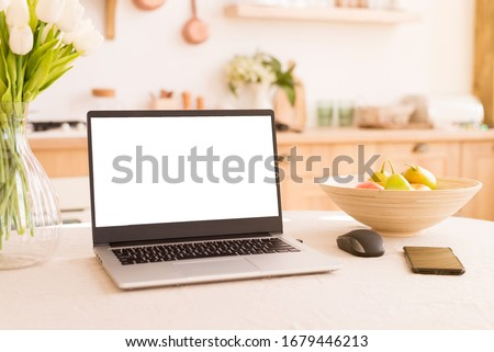 Front view of white screen laptop in kitchen with soft and warm light. Remote work. freelance. flowers and fruits on the table. Work from home. Telework. Copy space #1679446213