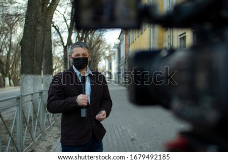 A middle- aged European journalist in a protective medical mask is reporting in a deserted city. #1679492185