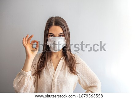 Coronavirus outbreak: Woman with a medical disposable mask to avoid contagious viruses, Showing OK sign. Corona virus prevention. Concept of coronavirus quarantine. Attention  #1679563558