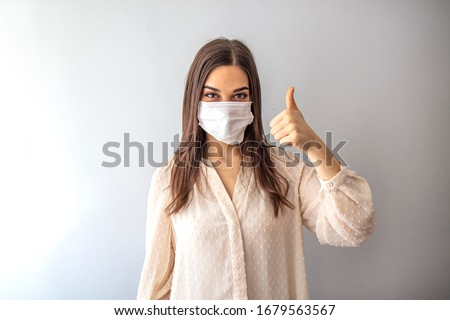 Young woman wearing medical face mask, studio portrait. Woman Wearing Protective Mask and Showing OK sign. Woman wearing surgical mask for corona virus.  #1679563567
