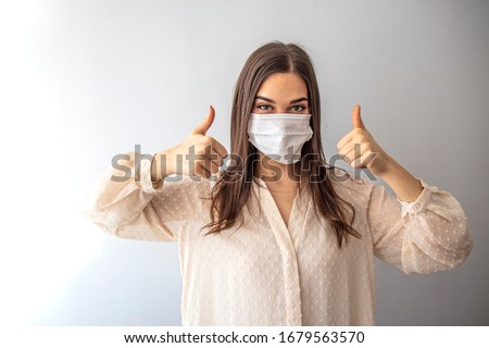 Beautiful caucasian young woman with disposable face mask. Protection versus viruses and infection. Studio portrait, concept with white background. Woman showing thumb up.  #1679563570