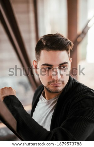 a man with dark hair a Jew with a beard and mustache in a gray t shirt black cardigan Cape with a serious expression poses under the bridge on an iron staircase against the background of pillars #1679573788