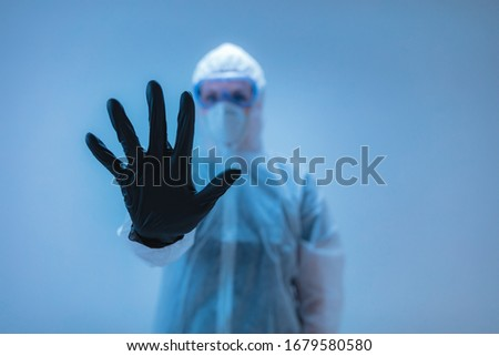 Medical doctor, scientist in full body suit for prevention from viruses and diseases holding a stop sign with hand - stop viral spreading. Royalty-Free Stock Photo #1679580580