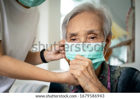 Elderly people have illness,fever and cough,infectious symptoms of flu,cold,pandemic of Covid-19,female caregiver wearing protective mask to sick senior woman,prevent outbreak,spread of Coronavirus Royalty-Free Stock Photo #1679586943