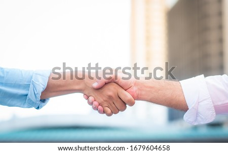Two roll up shirt sleeves businessman shaking hands agreement with blurred building background, successful business collaboration and teamwork,Team agreement in hands gesture communication #1679604658