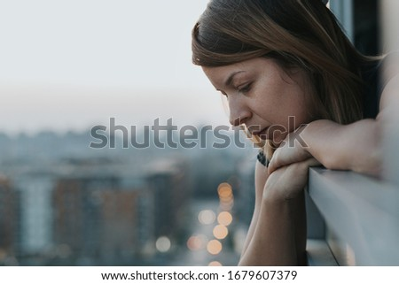 Young sad woman looking outside through balcony of an apartment building #1679607379
