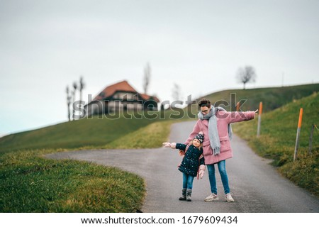 picture of lovely young caucasian female with pretty face, short dark hair, big eyes walks with her child and rejoices