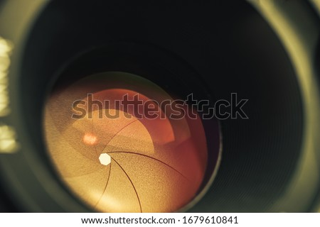 Beautiful camera lens with orange  light of glass. Background pattern for design.