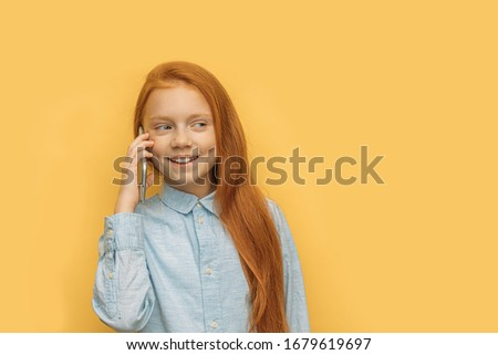 cheerful positive caucasian kid girl talk on phone with friend. happy girl with long red hair talk with friend, share news. isolated yellow background