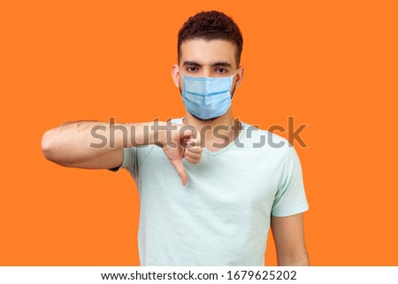 Thumbs down! Portrait of frustrated dissatisfied man with medical mask in casual white t-shirt showing dislike gesture, disapproval negative sign. indoor studio shot isolated on orange background #1679625202