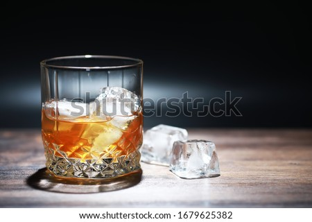 A glass of strong alcoholic drink with ice on wooden bar counter. Whiskey with ice cubes. Glass with a chilled drink. #1679625382