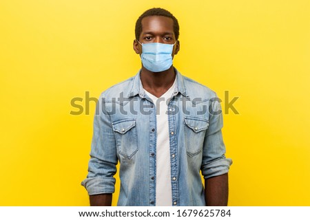 Portrait of serious self-assertive handsome man with medical mask with rolled up sleeves looking smart and professional, freelancer or employee. indoor studio shot isolated on yellow background #1679625784