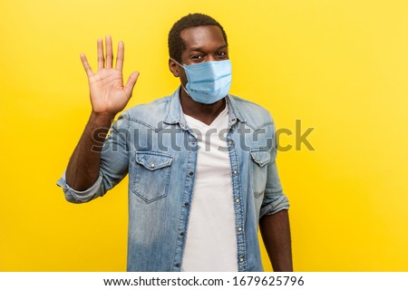 Hello! Portrait of positive handsome man with medical mask with rolled up sleeves smiling friendly and waving hand saying hi, welcoming gesture. indoor studio shot isolated on yellow background Royalty-Free Stock Photo #1679625796