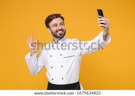Smiling young bearded male chef cook or baker man in white uniform shirt isolated on yellow background. Cooking food concept. Mock up copy space. Doing selfie shot on mobile phone, showing OK gesture