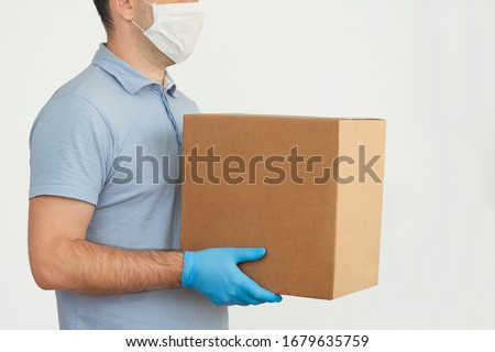 Delivery man holding cardboard boxes in medical rubber gloves and mask. copy space. Fast and free Delivery transport . Online shopping and Express delivery . Quarantine  #1679635759