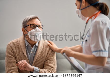 Doctor and senior man wearing facemasks during coronavirus and flu outbreak. Virus and illness protection, home quarantine. COVID-2019 Royalty-Free Stock Photo #1679644147
