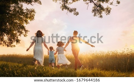 Happy family on summer walk! Mother, father and daughters walking in the Park and enjoying the beautiful nature. #1679644186