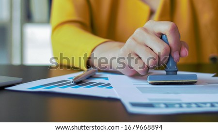 Close-up woman hand woman Stamping  With Approved Stamp On Document At Desk #1679668894