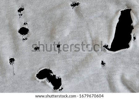 Gray white fabric with many holes. Texture of an old dirty ragged t shirt. Grunge damaged cloth on black background. Crumpled torn rag. Copy space #1679670604