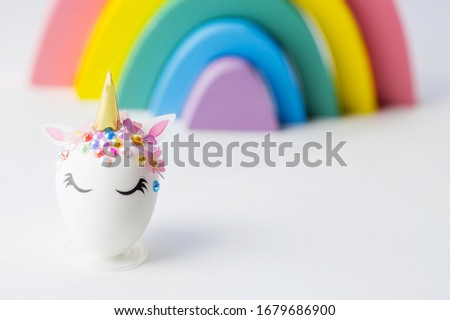 Minimal easter concept. Easter eggs in the shape of a unicorn on a rainbow background. Flat lay. Copy space for text. The portfolio has more Easter pictures.