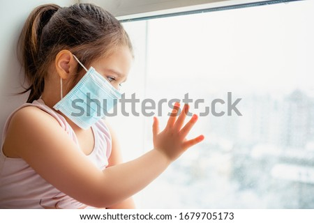 Little european girl wearing mask for protect pm2.5 and Covid-19. Sick child Little girls look at the window with longing on the street . Copy  space. sadness child at home in isolation        #1679705173