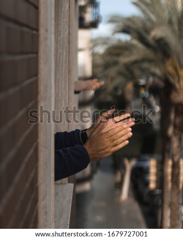 Hands clapping in window for coronavirus doctors Royalty-Free Stock Photo #1679727001