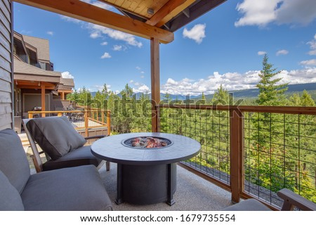 Amazing balcony patio with fire pit and forest and mountains view. Dream come true home exterior. New American architecture. Comfortable and beautiful home details. #1679735554