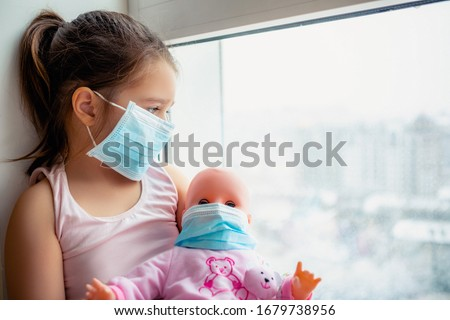 Little girl with doll wearing a protective mask. Copy space. Sadness kid at home in isolation. Sick child Little girls look at the window with longing on the street                         #1679738956
