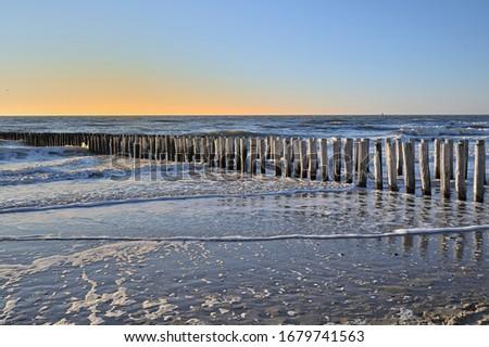 Breakwaters on a winter beach in Vlissingen Holland Royalty-Free Stock Photo #1679741563