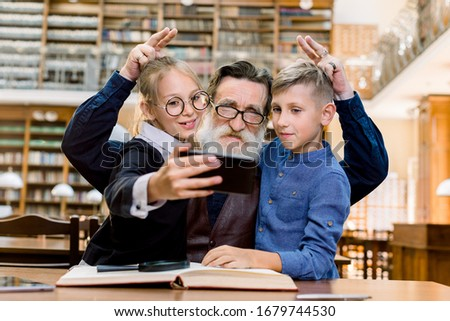 Funny photo of happy laughing teen granddaughter with grandson making photo selfie with their elegant handsome old granddad with funny finger gestures, library interior on the background