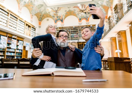 Happy family, old bearded grandfather and grandchildren are sitting at the table in vintage library, while posing for selfie photo on smartphone, having fun, being excited and proud