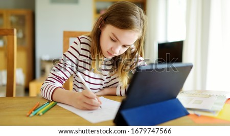 Preteen schoolgirl doing her homework with digital tablet at home. Child using gadgets to study. Education and distance learning for kids. Homeschooling during quarantine. Stay at home entertainment. #1679747566