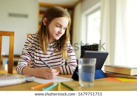 Preteen schoolgirl doing her homework with digital tablet at home. Child using gadgets to study. Education and distance learning for kids. Homeschooling during quarantine. Stay at home entertainment. #1679751751