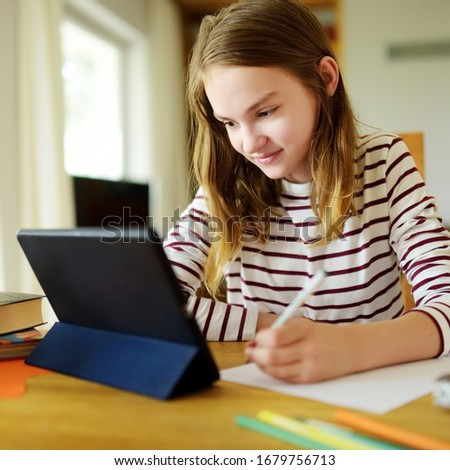 Preteen schoolgirl doing her homework with digital tablet at home. Child using gadgets to study. Education and distance learning for kids. Homeschooling during quarantine. Stay at home entertainment. #1679756713