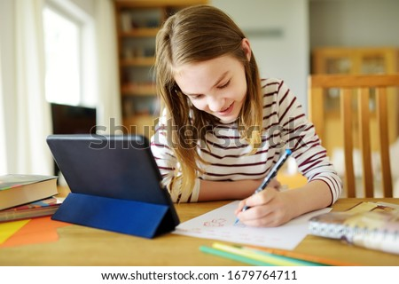 Preteen schoolgirl doing her homework with digital tablet at home. Child using gadgets to study. Education and distance learning for kids. Homeschooling during quarantine. Stay at home entertainment. #1679764711