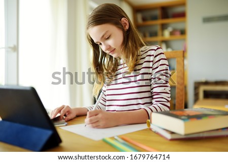 Preteen schoolgirl doing her homework with digital tablet at home. Child using gadgets to study. Education and distance learning for kids. Homeschooling during quarantine. Stay at home entertainment. #1679764714