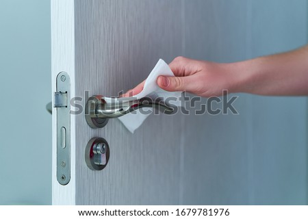 Person disinfects and cleans door handle with antibacterial wet wipes to protect against viruses, germs and bacteria during coronavirus outbreak and flu covid ncov epidemic. Clean home  Royalty-Free Stock Photo #1679781976