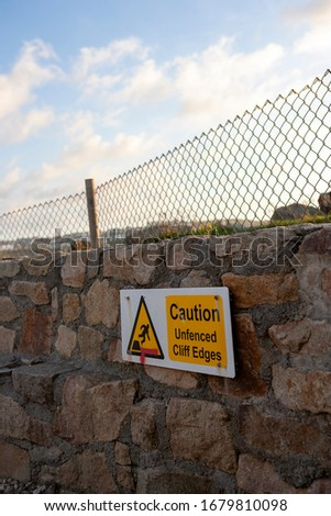 cliff warning sign on fenced stone wall #1679810098