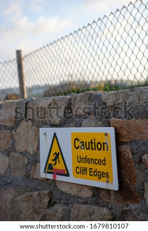 cliff warning sign on fenced stone wall #1679810107