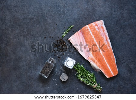 Fresh salmon filet and spices on a concrete black background. Ingredients for cooking. #1679825347